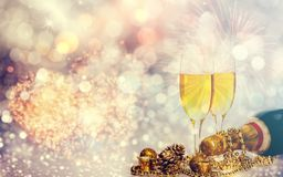 Champagne glasses on sparkling background. Glasses with champagne and Christmas decoration against fireworks and holiday lights - Celebrating the New Year Royalty Free Stock Images