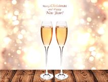 The champagne glasses stand on a wooden surface. Festive bokeh background Golden color, wooden boards and glasses of champagne. There is a place for text and Stock Photos