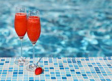 Champagne glasses with strawberry. Rossini cocktail. Summer pool. Champagne glasses with strawberry on turquoise background. Rossini cocktail. Summer pool party stock images