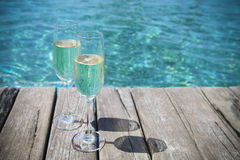 Champagne glasses by swimming pool Royalty Free Stock Images