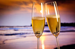 Champagne glasses on tropical beach - exotic New Year. Champagne glasses on tropical beach at sunset - exotic New Year Stock Photography