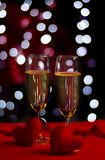 Champagne in glasses of two in romantic valentine concept with heart shaped fabric on red and light bokeh background stock photos