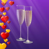 Champagne glasses, yellow and red hearts like Inflatable balloons dark on background with rays. Glasses of champagne with rays of light on background. Champagne Stock Photos