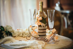 Champagne-glazen met een huwelijksdecoratie en een fles champagne Stock Afbeeldingen