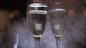 Champagne in glazen in nachtclub met het partying van mensen op achtergrond stock videobeelden