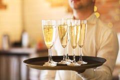 Champagne-glazen op dienblad Partij en gebeurtenisconcept Stock Afbeelding