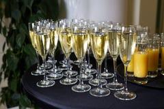 Champagne in glazen wordt gegoten die zich naast jus d'orange bevinden dat stock afbeelding