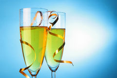 Champagne and gold streamer. Two glasses of champagne with gold streamer over blue background Stock Image