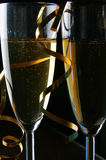 Champagne and gold streamer. Two glasses of champagne and gold streamer over black background Royalty Free Stock Photos