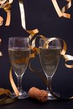 Champagne and gold streamers. Two glasses of champagne and gold streamers on black Stock Photos