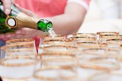 Champagne häller in i exponeringsglas Arkivbild