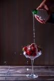 Champagne hälls in i ett exponeringsglas med jordgubbar Arkivbilder