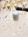 Champagne hälls in i exponeringsglas Fotografering för Bildbyråer