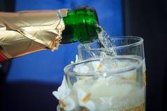 Champagne hälls in i exponeringsglas som gifta sig bröllopsresa Royaltyfria Bilder