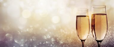 Champagne for a happy new year. On glittering gold silver bokeh background stock photos