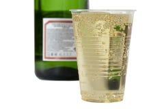 Champagne i disponibel kopp på den suddiga flaskan för bakgrund av Royaltyfria Bilder