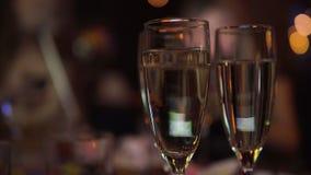 Champagne i exponeringsglas i nattklubb med att festa folk på bakgrund stock video