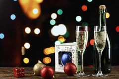 Champagne i exponeringsglas och i en flaska och leksaker på julgranen på bakgrunden av bokeh arkivbild