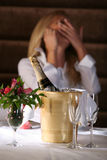 Champagne and Ice Bucket. Image of a champagne bottle in a  bucket of ice, two glasses and a flowered centerpiece with a happy woman in the background Stock Photography