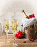 Champagne & Ice Bucket. Two glasses of champagne with ice bucket and red roses Royalty Free Stock Photo