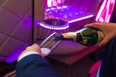 Hand fills champagne flutes in the limusine with back light stock image