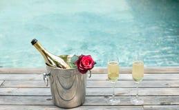 Champagne imbottiglia il vetro del champagne e del secchiello del ghiaccio nuotando la p immagini stock