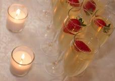 Champagne, jordgubbar och stearinljus Arkivbilder