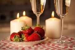 Champagne, jordgubbar och stearinljus. Royaltyfri Foto
