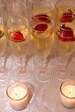 Champagne, jordgubbar och stearinljus i rader Royaltyfri Bild