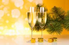 Champagne jul sörjer fattar och små gåvor, på gul bakgrund Royaltyfri Bild