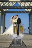 Champagne and married couple. Pair of flute glasses of champagne with Caucasian bride and groom blurred in background Stock Photos