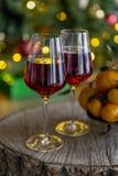 Champagne med mandariner på träbrädet, julträd bakom royaltyfria bilder