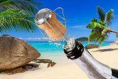 Champagne mit spritzt auf dem tropischen Strand lizenzfreies stockbild