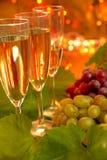 Champagne mit Trauben auf Goldhintergrund. Stockfotos