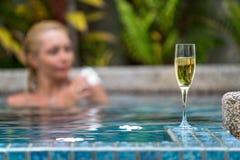 Champagne nära simbassäng på en bakgrund av en härlig kvinna Arkivfoton