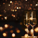 Champagne for a new year. Champagne glasses for a new year against a dark background with gold shimmering light Royalty Free Stock Image