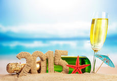 Champagne and New year sign. On sandy beach Stock Photo