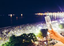 Champagne at NYE in Copacabana, Brazil. Hand holding champagne glass overlooking Copacabana Beach in Rio de Janeiro, Brazil at New Years Eve Stock Photography