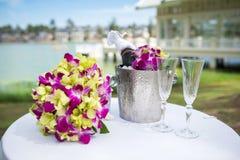 Champagne och ett exponeringsglas av champagne på tabellen för bröllopet Royaltyfri Fotografi