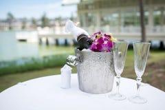 Champagne och ett exponeringsglas av champagne på tabellen för bröllopet Royaltyfria Bilder