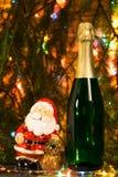 Champagne på bakgrunden av girlander med Santa Claus Royaltyfri Foto