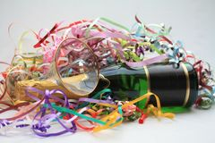 Champagne party. A bottle of champagne, a pile of colored ribbons and a champagne flute Stock Image