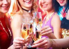 Champagne at party. Beautiful girls clink glasses of champagne at a party. unrecognizable people royalty free stock photos