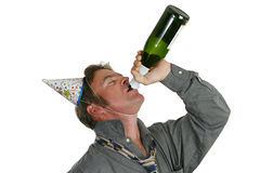 Champagne Party Guy. A good-looking man drinking champagne from a bottle and wearing party hats Stock Image