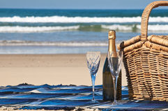 Champagne Picnic. Picnic blanket,champagne,picnic basket and a beautiful tropical beach Royalty Free Stock Photo