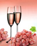 Champagne in pink color. Two flutes of pink champagne with pink grapes on pink background royalty free stock photo