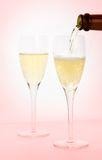 Champagne in a pink haze. Champagne, one glass being poured, on pink.  Shallow DOF, focus on right champagne glass bubbles Stock Images