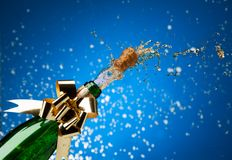 Champagne plash and snow. Popping cork from Champaign bottle with gold bow on it and splashes all around the blue background royalty free stock photo