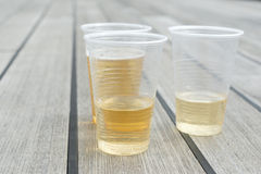 Champagne in plastic cups. On wooden floor Royalty Free Stock Photography