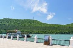 Champagne Pleasure fartyg på pir av den pittoreska bergsjön Abrau Pelaren med villkor av vatten går Fotografering för Bildbyråer